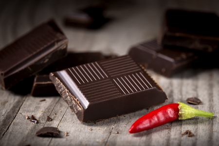 confiserie: Chopped Chocolate with Red Chilli Pepper on wooden background closeup. Chunks of Broken dark chocolate bar on wood table macro.