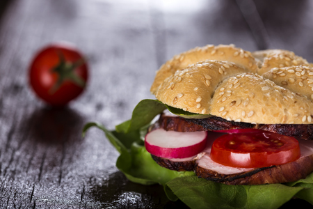 panino: Tasty sandwich stuffed with ham and vegetables on wooden background