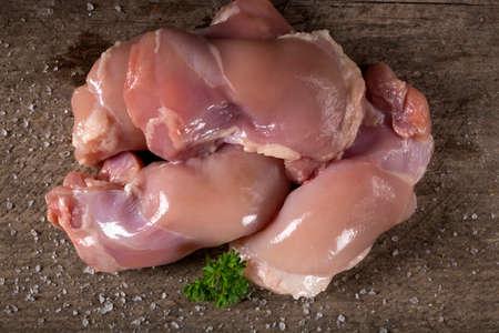 protien: Raw boneless chicken thighs on a wooden background board Stock Photo