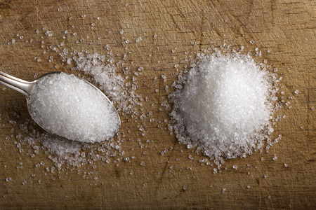 granulated: Close-up of granulated sugar in silver spoon and one pile of white sugar