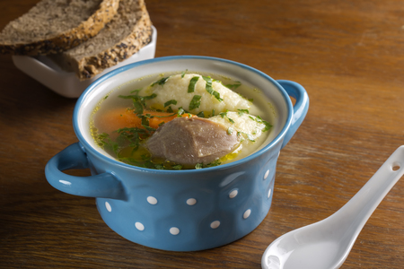 kneidl: Chicken soup with dumplings and bread in blue bowl on wooden table