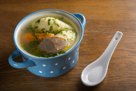 kneidl: Chicken soup with dumplings in blue bowl on wooden table
