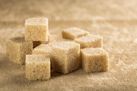 cane sugar: Brown cane sugar cubes on a brown background