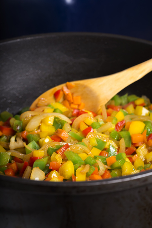 aceite de cocina: Bell peppers (pepperoni) pan-fried with carrot and onion wooden spoon