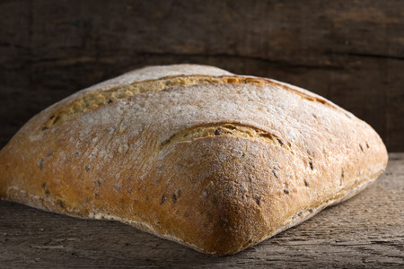Homemade fresh baked bread loaf over rustic wooden background