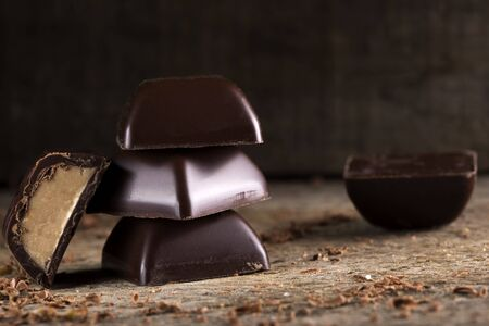 Pile of chocolate pieces on wooden rustic background Stock Photo