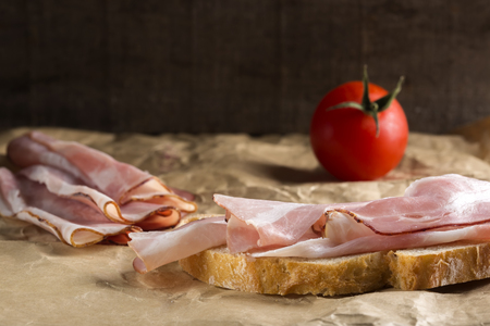 tomate: Slice of bread with ham and one tomato over paper background