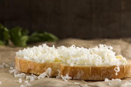Fetta di pane con burro e formaggio grattugiato su carta