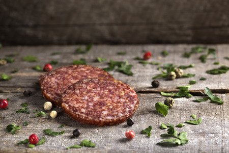 salami slices: Salami slices with parsley and peppercorns over wooden background