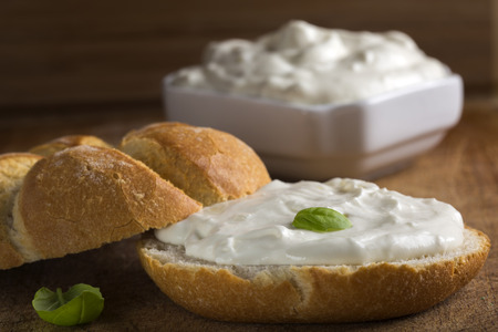 Healthy Organic Whole Grain Bagel with Cream Cheese over wooden background