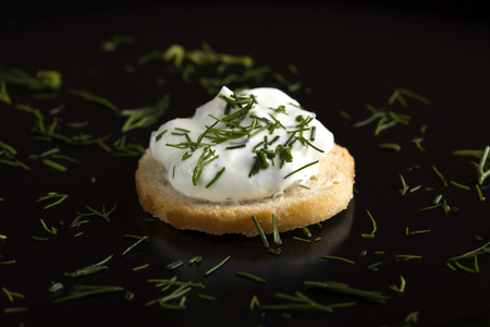 Close up of a wheat cracker with cream cheese and a dill garnish