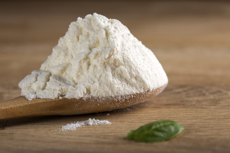 un cook: White flour in spoon on wooden background with shallow depth of field