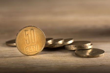 Stacks of Romanian fifty bani coins on wooden table, with selective focus Stock Photo