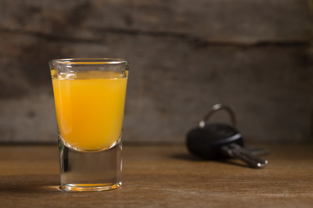 drink and drive: Car keys with one shot glasses over wood background - drink drive concept Stock Photo