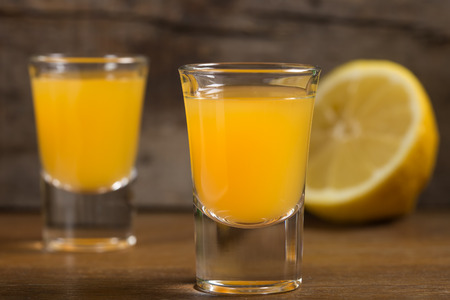 fruit of the spirit: Two shot glasses of vodka with orange juice over wooden background Stock Photo