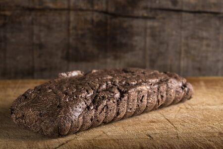 Piece of chocolate halvah over wooden background