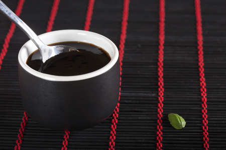 Bowl of Soy Sauce over black bamboo rug Stock Photo