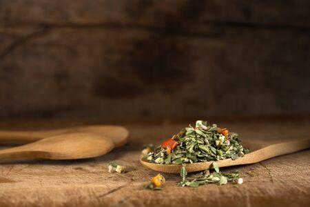 legumbres secas: Cuchara de madera con el condimento italiano - orégano seco con tomillo, albahaca y verduras