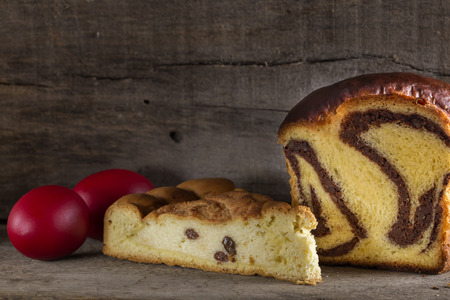 Romanian cakes Cozonac with smashed nuts and Pasca with cheese and raisins and traditional colored easter eggs Stock Photo