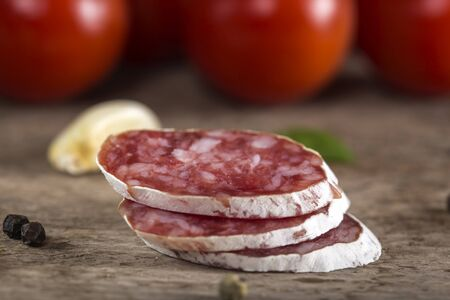 salami slices: Close up of Italian salami slices with spices and vegetables over rustic wooden background