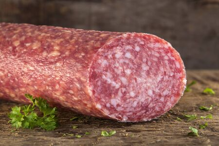 italian salami: Fresh Italian Salami on wooden board with herbs