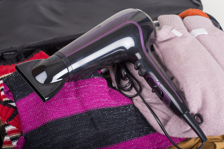 Modern hair dryer on travel bag with clothes Stock Photo