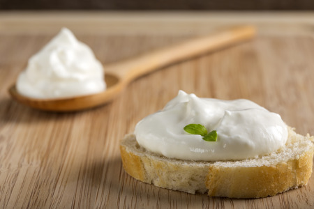 galletas integrales: Fresh bread with creamy spread and herbs on wooden background