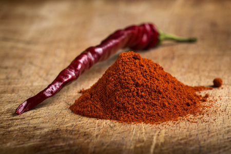 capsaicin: Red hot paprika powder heap and one dried chilli on wooden background