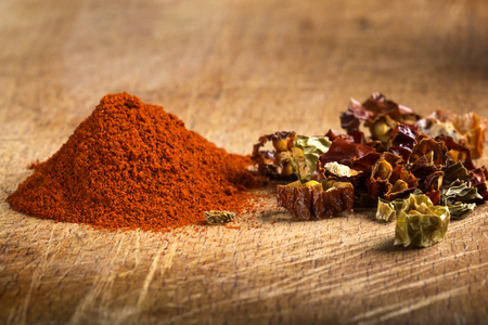 chiles secos: Red hot paprika powder and pieces of dried chiles on wooden background Foto de archivo