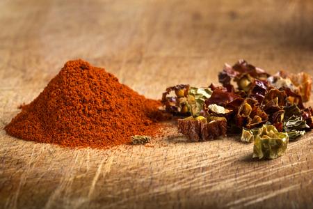 chiles secos: Rojo pimentón en polvo caliente y trozos de chiles secos en el fondo de madera Foto de archivo