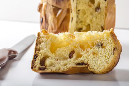 Slice of panettone with knife on white table