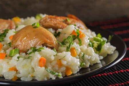 Pilaf - Romanian traditional food made with chicken, rice and vegetable on dark background