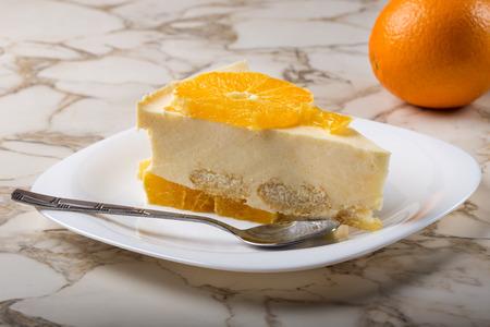 One slice of homemade orange cake on plate with teaspoon  Stock Photo