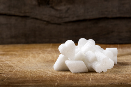 Heap of different sugar cubes shapes on wooden brown background