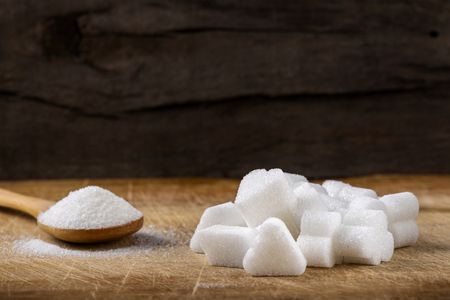 trapeze: Heap of different sugar cubes shapes and one wooden spoon filled with sugar in background