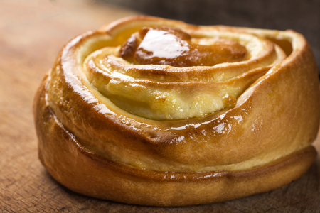 danish: Sweet snail cake filled with nut cream and honey on wooden background