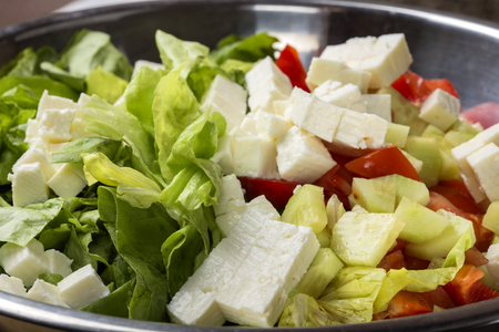 Fresh raw ingredients and romanian white cheese telemea for salad in bowl Stock Photo