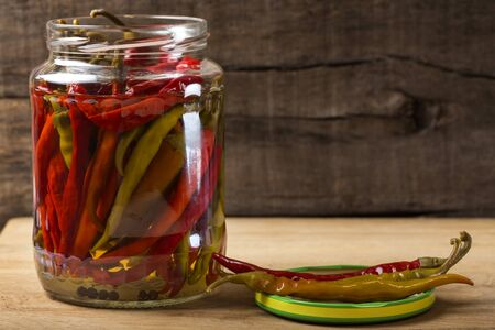 Marinated hot peppers in jar over wooden background Stock Photo
