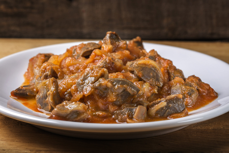 giblets cooked: Chicken gizzard stew on plate on wooden rustic background