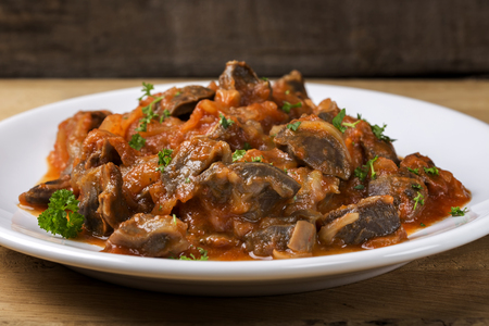 Chicken gizzard stew on plate with herbs on wooden rustic background