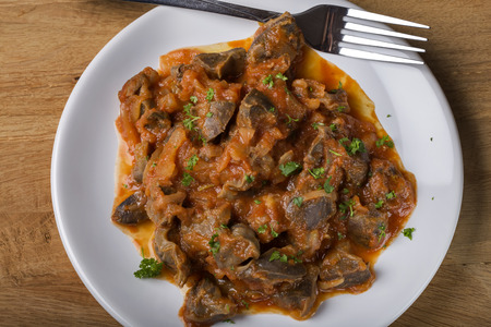 Chicken gizzard stew on plate with fork on wooden rustic background