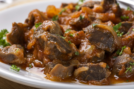 giblets cooked: Close up of chicken gizzard stew on plate with herbs on wooden rustic background