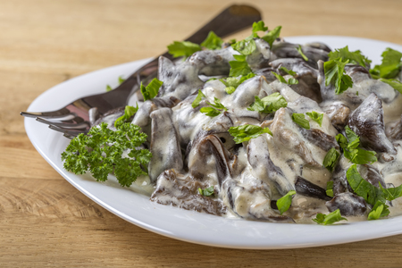 Mushrooms stew with sour cream on plate Stock Photo