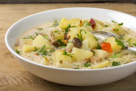Mushrooms soup with sour cream and potatoes on plate