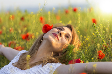 ring stand: Woman in white dress relaxing in a full field of poppies