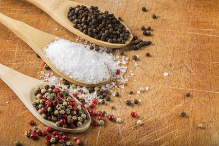flavouring: Wooden spoons with sea salt and peppercorns on wooden background with copy space. Macro with shallow dof.