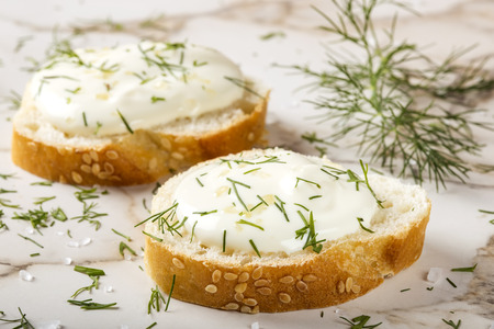Sesame bagel with cream cheese, dill and salt on table