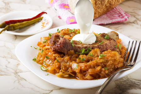 Cabbage stew with Smoked Pork Ribs, cream  and green parsley Served in white plate with pickled chili peppers and bread