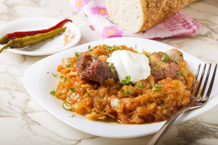 Cabbage stew with Smoked Pork Ribs, cream and green parsley Served in white plate with pickled chili peppers and bread Stock Photo