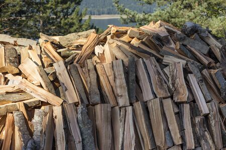 Firewood logs stacked in piles outside cottage Stock Photo